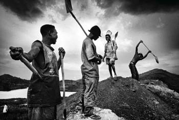 Labourers shovelling hillocks of extracted coal